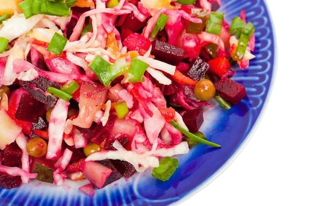 Salade de légumes sur une assiette avec une bordure bleu foncé