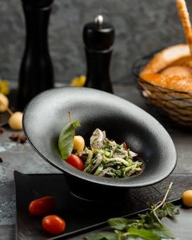 Salade de légumes en assiette noire