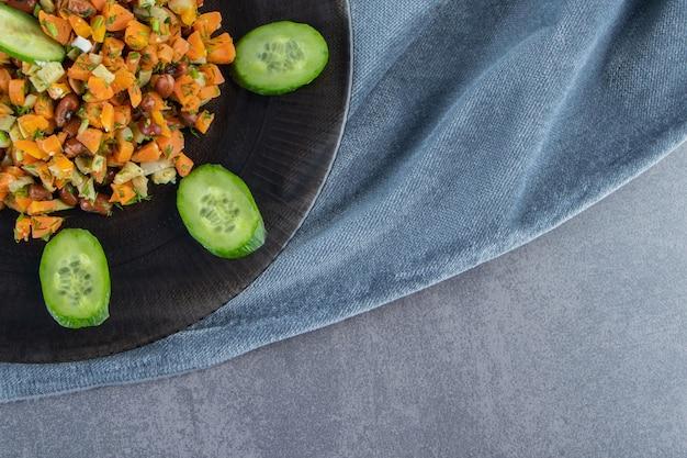 Salade de légumes sur une assiette sur une serviette sur la surface en marbre