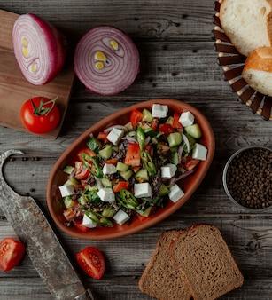 Salade de légumes au fromage vue de dessus dans un bol en poterie