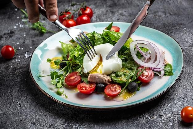Salade de légumes au thon, oeuf poché, laitue, cerise, tomates et olives