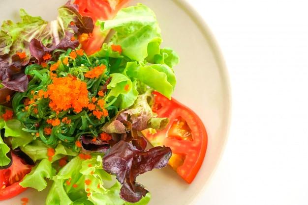 Salade de légumes aux algues japonaises et œufs de crevettes sur une surface blanche