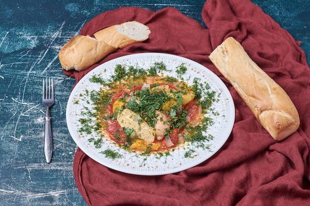 Salade de légumes aux herbes et épices servie avec baguette.