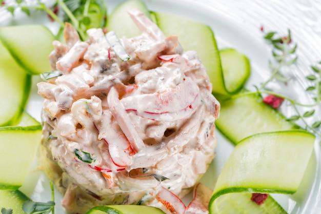 Salade de légumes aux légumes, viande et herbes sur plaque blanche