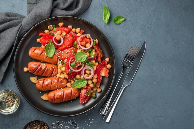 Salade de légumes aux pois chiches et saucisses dans une assiette noire sur fond graphite