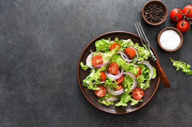 Salade de légumes aux tomates, oignons rouges et sauce sur fond noir, vue du dessus