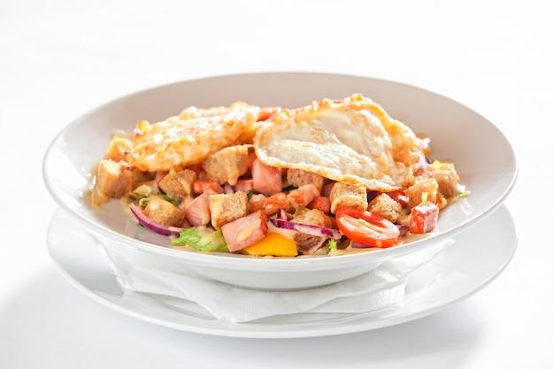 Salade de légumes, bacon et œufs au plat