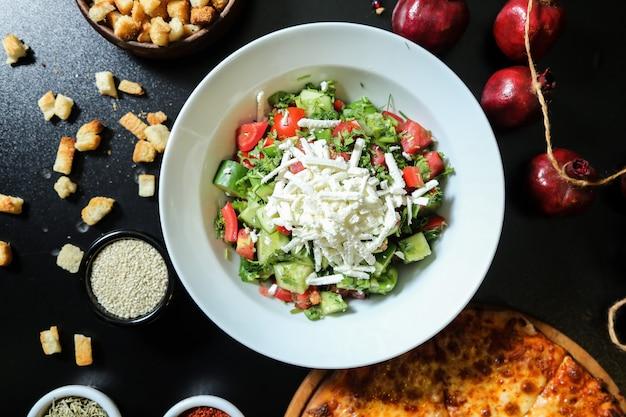 Salade de légumes de berger avec fromage haché vue d'en haut