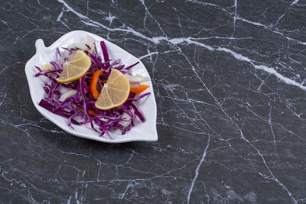 Salade de légumes biologiques frais sur plaque blanche.