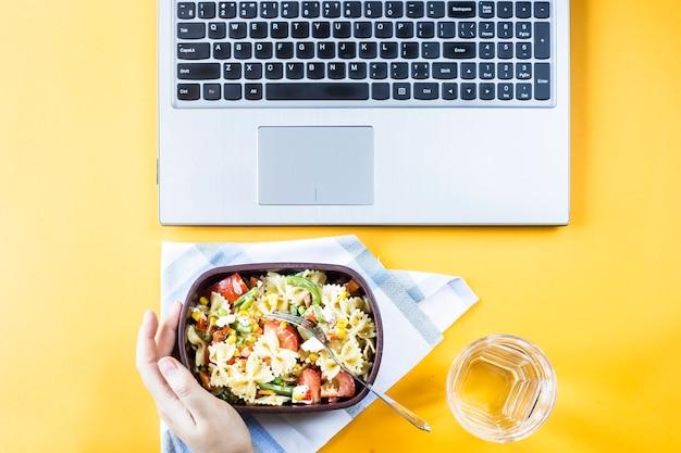 Salade de légumes avec des bols de macaronis avec du fromage dans un récipient pour le déjeuner