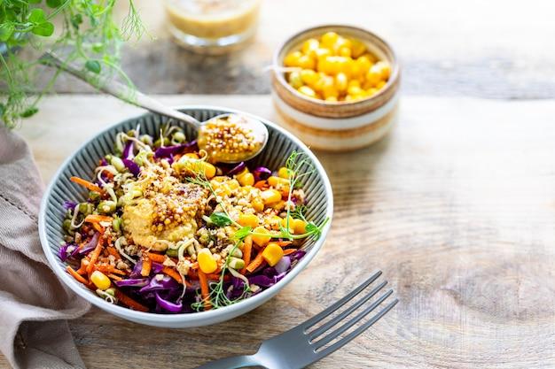 Salade de légumes de chou rouge frais aux carottes, oignons, maïs, semis de mungo dans une assiette sur fond de bois. mise au point sélective. copiez l'espace. horizontal