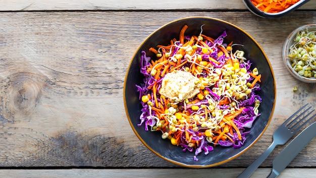 Salade de légumes de chou rouge frais aux carottes, oignons, maïs, semis de mungo dans une assiette sur fond de bois. mise au point sélective. vue de dessus. copiez l'espace. horizontal