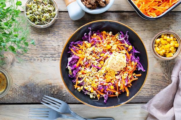 Salade de légumes de chou rouge frais aux carottes, oignons, maïs, semis de mungo dans une assiette sur fond de bois. mise au point sélective. vue de dessus.