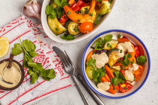 Salade de légumes cuits au four avec tahini en plaque blanche, fond blanc, vue de dessus. concept de restauration propre.
