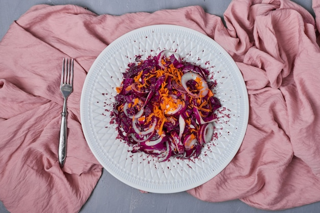 Salade de légumes dans une assiette blanche sur bleu