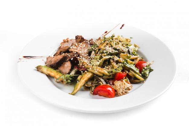 Salade de légumes dans une assiette blanche sur fond blanc