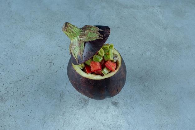 Salade de légumes dans une aubergine sculptée violette.