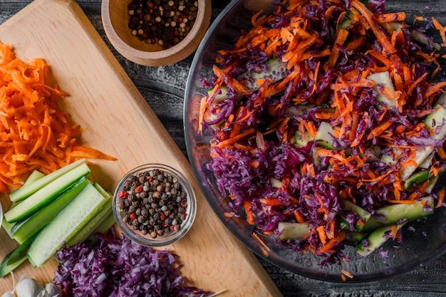 Salade de légumes dans un bol avec d'autres légumes hachés sur une planche à découper en gros plan sur un fond en bois foncé