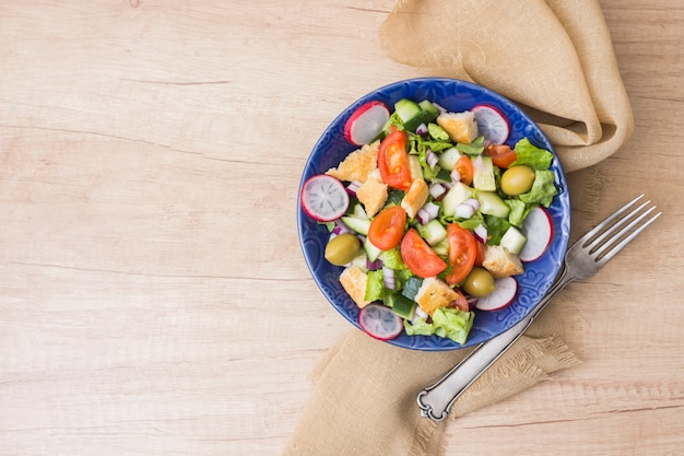 Salade de légumes dans un bol sur une table en bois