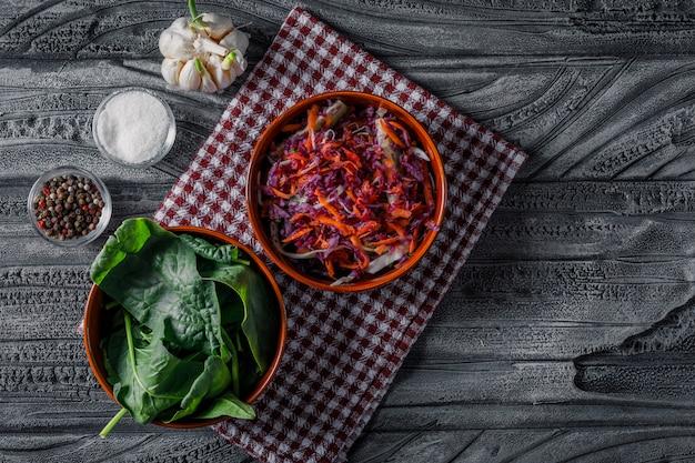 Salade de légumes dans des bols avec vue de dessus de verts sur un tissu de pique-nique et fond en bois foncé.