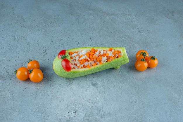 Salade de légumes dans une courgette sculptée sur fond bleu.