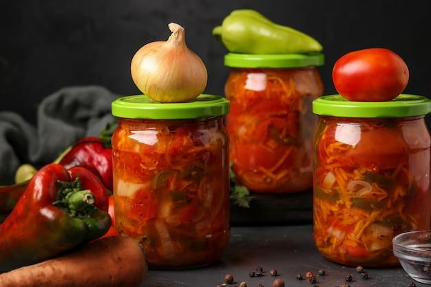 Salade de légumes dans des pots pour l'hiver de tomates, carottes, oignons et poivrons, disposition horizontale