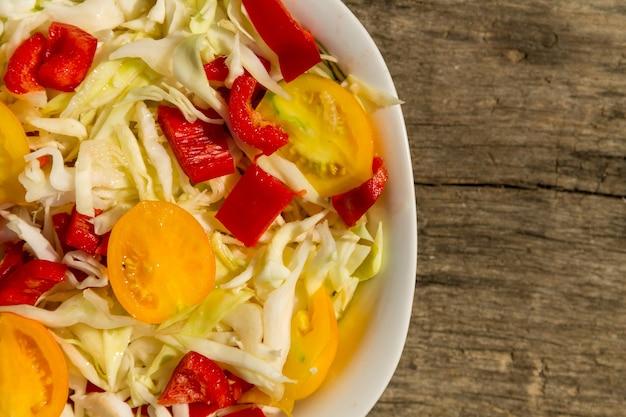 Salade de légumes frais au chou, tomates jaunes et poivrons rouges sur table en bois rustique. vue de dessus