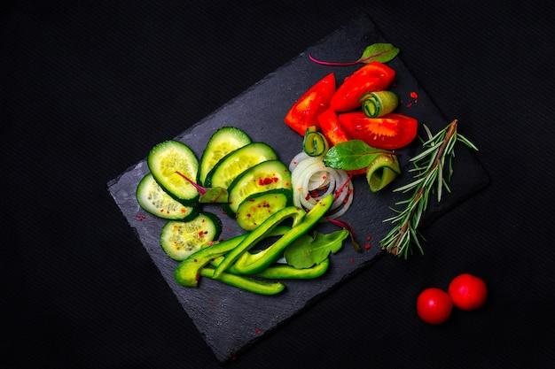 Salade de légumes frais au chou violet, chou blanc, laitue, carotte dans un bol d'argile sombre sur fond noir. vue de dessus