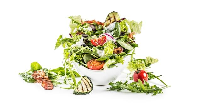 Salade de légumes frais avec bacon frit tomates olives roquette courgette tzatziki vinaigrette et huile d'olive isolé sur fond blanc.