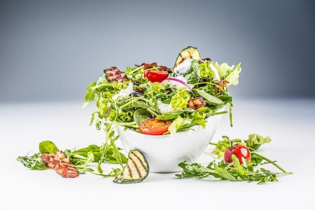Salade de légumes frais avec bacon frit tomates olives roquette courgette vinaigrette tzatziki et huile d'olive.