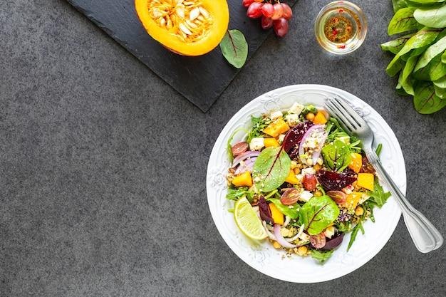 Salade de légumes frais avec betterave, roquette, oignon rouge, oseille, pois chiches, citrouille et raisins dans une assiette blanche sur un tableau noir. vue de dessus