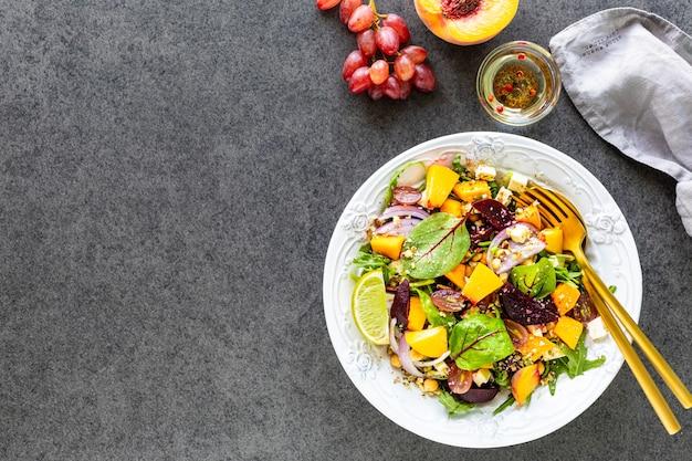 Salade de légumes frais avec betteraves, roquette, oignon rouge, oseille, pois chiches, pêche et raisins dans une assiette blanche
