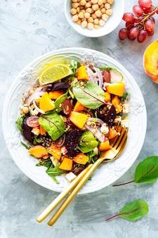 Salade de légumes frais avec betteraves, roquette, oignons rouges, oseille, pois chiches, pêches et raisins dans une assiette blanche sur pierre blanche. vue de dessus