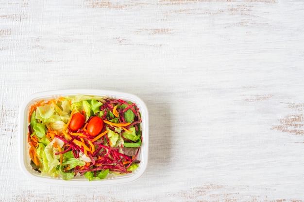 Salade de légumes frais sur bois blanc rouillé.