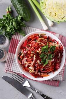Salade de légumes frais: chou, betterave, carotte, concombre, oignon et persil dans un bol blanc sur surface grise, format vertical, vue du dessus