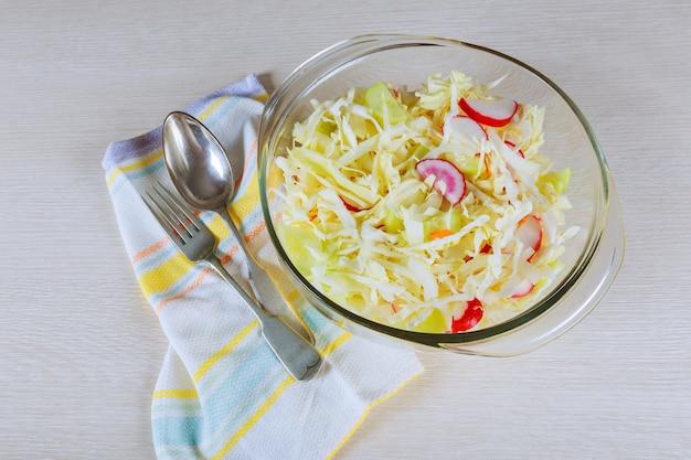 Salade de légumes frais avec chou violet, chou blanc, laitue, carotte sur une plaque blanche sur fond blanc en bois.