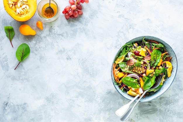 Salade de légumes frais et de citrouille dans une assiette sur une surface en pierre blanche