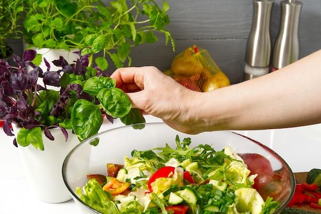 Salade de légumes frais dans une assiette sur une table. bol de salade avec légumes et légumes verts sur tableau blanc. femmes préparant une salade de légumes - gros plan. cuisine domestique. la nourriture végétarienne.