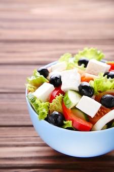 Salade de légumes frais sur un fond en bois marron