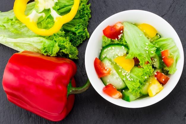 Salade de légumes frais sur fond noir, vue de dessus.