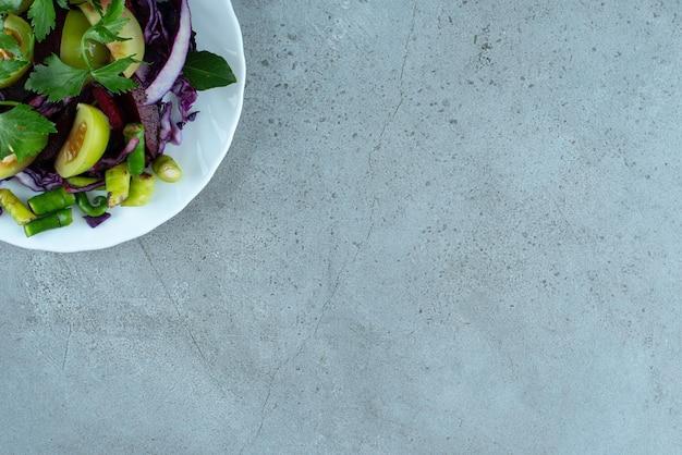 Salade de légumes frais sur plaque blanche.
