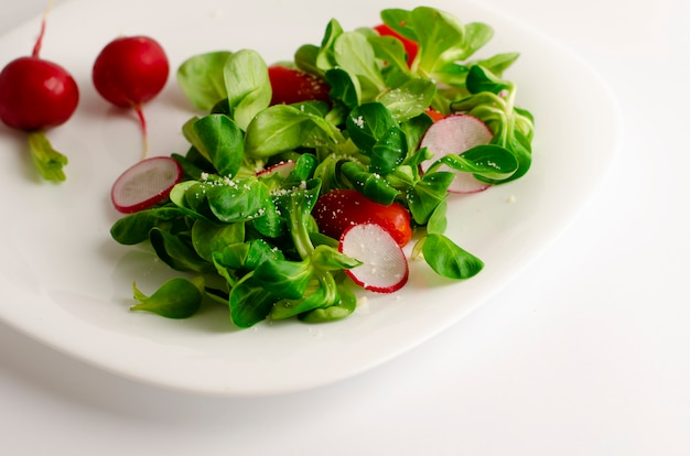 Salade de légumes frais de radis, tomates et salade de maïs ou valerianella locusta.