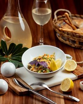 Salade de légumes garnie de zeste de citron orange et de tranches de citron