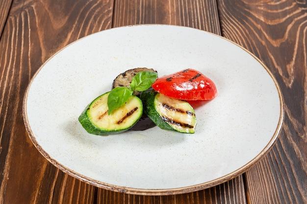 Salade de légumes grillés sur une table en bois plaque blanche