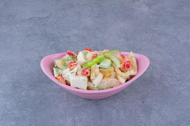 Salade de légumes hachés et d'herbes sur une surface bleue