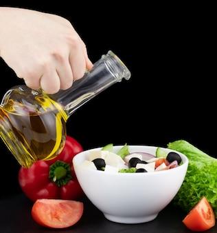 Salade de légumes à l'huile d'olive versée d'une bouteille.