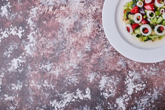 Salade de légumes avec des ingrédients hachés et hachés sur une plaque blanche
