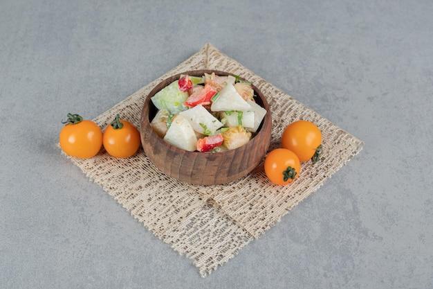 Salade de légumes avec des ingrédients mélangés dans une tasse en bois.