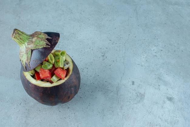 Salade de légumes à l'intérieur d'une aubergine sculptée.