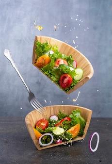 Salade de légumes en lévitation. salade végétarienne fraîche dans un bol en bois coupé en deux.